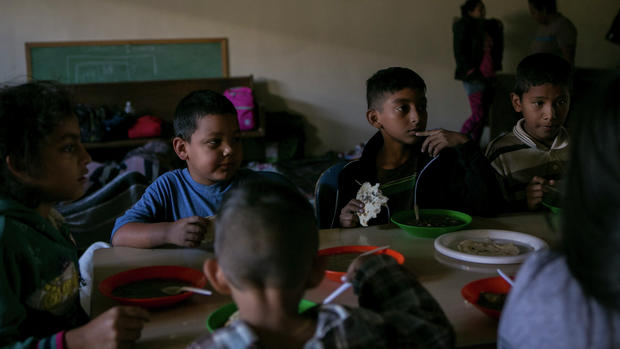 Children sit for breakfast after spending the night sleeping on church pews or the floor in a shelter in Tijuana, Mexico.